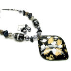 Elegant in black and gold with a silver shine, 20 inch necklace with 3 inch drop and earring to match